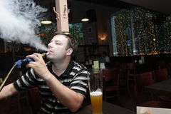 Man in shisha house Royalty Free Stock Image