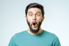 Man with shocked, amazed expression. On gray background Stock Photography