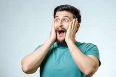 Man with shocked, amazed expression. On gray background Royalty Free Stock Image