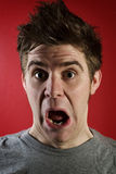 Man with shocked expression. Young man with shocked expression against red background Royalty Free Stock Photos