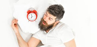 Man with shocked face lies on pillow near alarm clock. Morning and overslept concept. Man sleep, morning, need to get up, white background, top view. Hipster Stock Photo