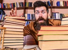 Man on shocked face between piles of books, while studying in library, bookshelves on background. Teacher or student. With beard sits at table with glasses Royalty Free Stock Photography