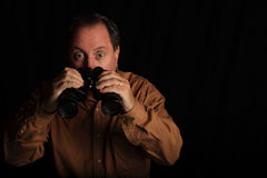 Man Shocked With a Large Pair of Binoculars. Man with a shocked look at what he see through a large pair of binoculars.  Black background, brown shirt Royalty Free Stock Photo