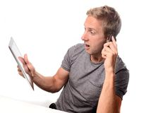 Man shocked on tablet and smart phone Royalty Free Stock Photos