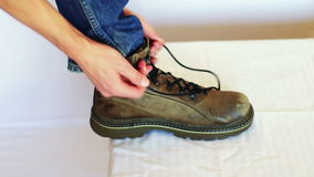 Man shoes laces. A man dressed in jeans, laces up his shoes on a white background stock video footage