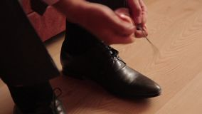 Man shoes shoes. Man ties the laces on black shoes stock footage