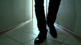 Man in shoes walks down a dirty corridor forward on camera, close-up