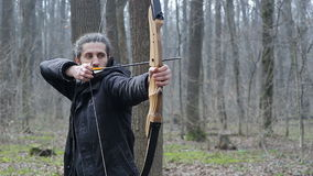 Man shoot with a bow in the forest. Man shoot with a recurve bow in the forest stock video footage
