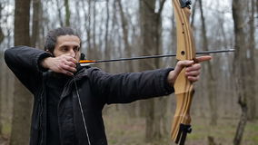 Man shoot with a bow in the forest stock footage