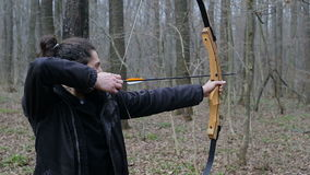 Man shoot with a bow in the forest. Man shoot with a recurve bow in the forest stock footage