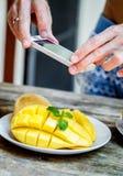 Man shoot on phone mango Royalty Free Stock Image