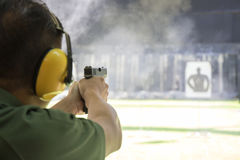 Man shooting automatic pistol to target in shooting range. Law enforcement aimimg and shooting gun in academy shooting range surround with smoke and copy space stock image