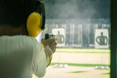 Man shooting automatic pistol to target in shooting range. Law enforcement aimimg and shooting gun in academy shooting range surround with smoke and copy space royalty free stock image