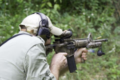 Man Shooting Carbine. Man shooting an AR15 carbine rifle. The brass ammunition cartridge is seen flying past the barrel Stock Photo