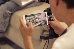Man shooting girl typing on laptop with cell phone camera. Close up view of shot on mobile phone Stock Images