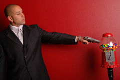 Man shooting gumball machine. Attractive man wearing a business suit pointing a gun at a gumball machine Royalty Free Stock Images