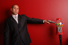 Man shooting gumball machine. Attractive man wearing a business suit pointing a gun at a gumball machine Royalty Free Stock Photo