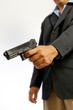 Man shooting a gun. A man wearing suit is pointing a gun down and triggering the firearm Royalty Free Stock Image