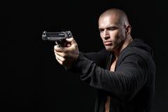 Man shooting gun isolated on black Stock Photos