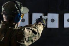 Man shooting. With gun at a target in shooting range Stock Images