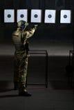 Man shooting. With gun at a target in shooting range Royalty Free Stock Photo