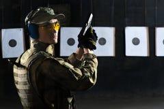 Man shooting. With gun at a target in shooting range Royalty Free Stock Photos