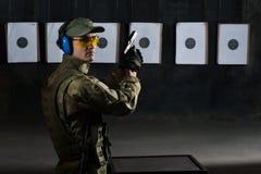 Man shooting. With gun at a target in shooting range Stock Photo