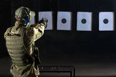 Man shooting. With gun at a target in shooting range Stock Photos