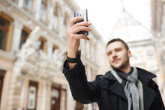 Man shooting magnificent architecture on phone while walking around city. Stock Photos