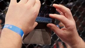 Man shooting MMA, mix fight or cage fighting on video using phone close up. Male hand shooting sporting event on. Smartphone. Man shooting photos in a crowd on Royalty Free Stock Photo