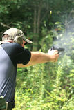Man Shooting Pistol - Sideview. Sideview of a man aiming a pistol at an off-camera target. Having just been fired, smoke rises from the barrel and surrounds the Stock Images