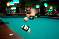 Man shooting pool. Man concentrating on hitting green half-ball in pool game royalty free stock photography