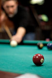 Man Shooting Pool. A young man lines up his shot as he breaks the balls for the start of a game of billiards. Shallow depth of field royalty free stock photos