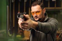 The man at the shooting range. Shooting a gun at shooting range royalty free stock photography