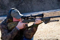 Man Shooting Rifle. Man sitting on the ground shooting a precision rifle at a distant target Stock Photography