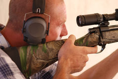 Man shooting rifle. Close up shot of a man wearing ear protection shooting a sniper rifle Royalty Free Stock Photography