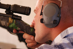 Man shooting rifle. Close up shot of a man wearing ear protection shooting a sniper rifle Royalty Free Stock Images