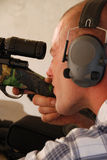 Man shooting rifle. Close up shot of a man wearing ear protection shooting a sniper rifle Stock Photos