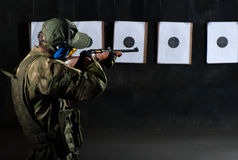 Man shooting. With rifle at a target in shooting range Stock Image