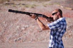 Man shooting shot gun. Man wearing a checked shirt shooting a double barreled shot gun Royalty Free Stock Photography