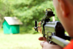 Man shooting a shotgun. Man aiming at a target and shooting an automatic rifle  for strikeball. Focus on the rifle sights Stock Image