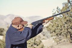 Man Shooting a Shotgun Hunting. An old man shooting a shotgun in the mountains. Hunting or target practice Royalty Free Stock Photos