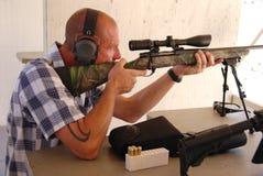 Man shooting sniper rifle. Man wearing ear protection shooting a sniper rifle Royalty Free Stock Photos
