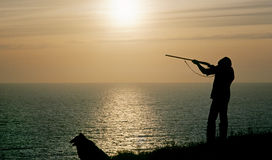 Man shooting at sunset. A farmer with a collie dog shoots grouse at sunset over a moor adjacent to the ocean in Cornwall Stock Photos