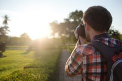 Man shooting sunset on his professional photocamera. View from the back Royalty Free Stock Photography