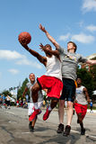 Man Shoots Against Defender In Outdoor Street Basketball Tournament. Athens, GA, USA - August 24, 2013: A young man jumps to get off a shot against a defender royalty free stock photo