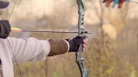 A man shoots a bow. Man aiming bow at target outdoors stock video footage