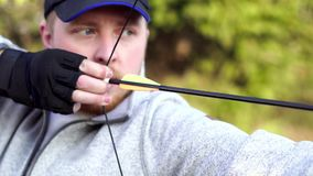 A man shoots a bow. Man aiming bow at target outdoors stock footage