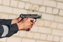 Man shoots from the gun. Man firing a bullet from a gun. frozen bullet Royalty Free Stock Images