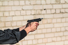 Man shoots from the gun. Man firing a bullet from a gun. frozen bullet Royalty Free Stock Photography